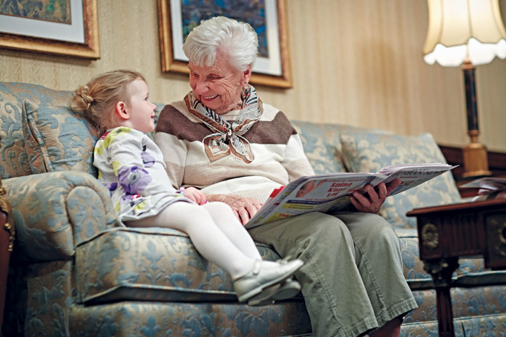 Assisted living at Brandywine Living - Elderly woman reading a book to a child while sitting ona couch