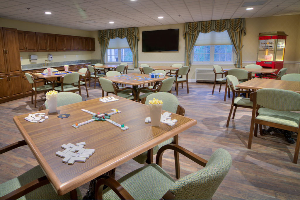 Escapades senior service with comfortable chairs, popcorn machine, and a television for guests to socialize and enjoy.