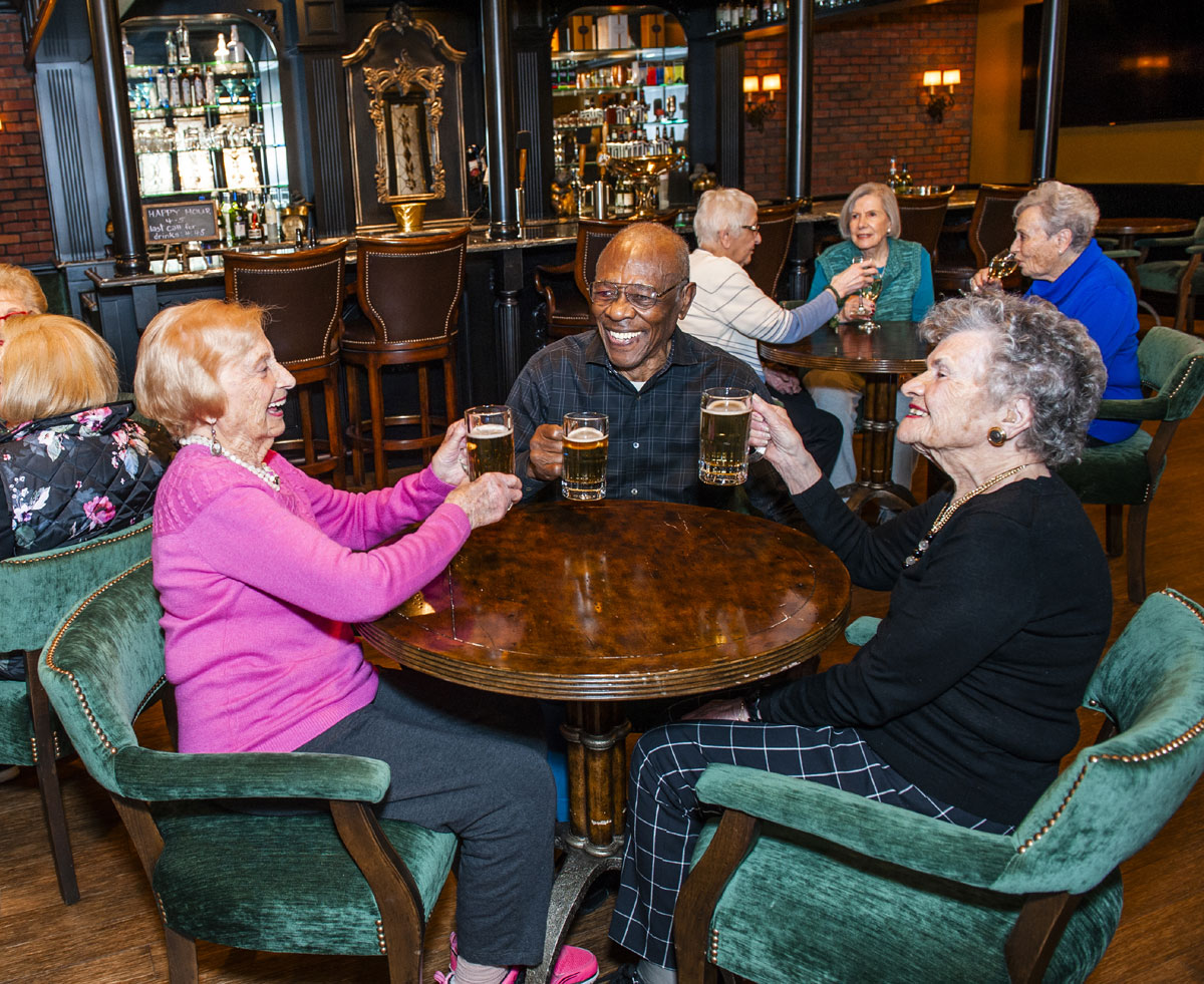 Independent Living at Brandywine Living - Three Brandywine residents in a Brandywine taproom cheersing their beer mugs