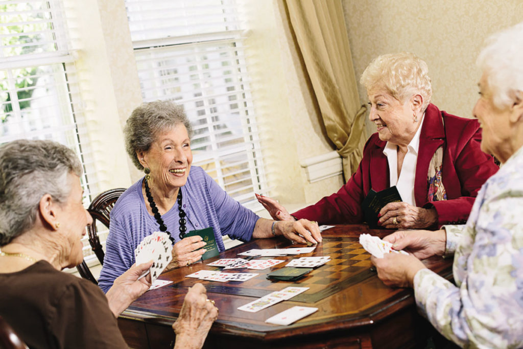 A group of ladies playing a card game and laughing.