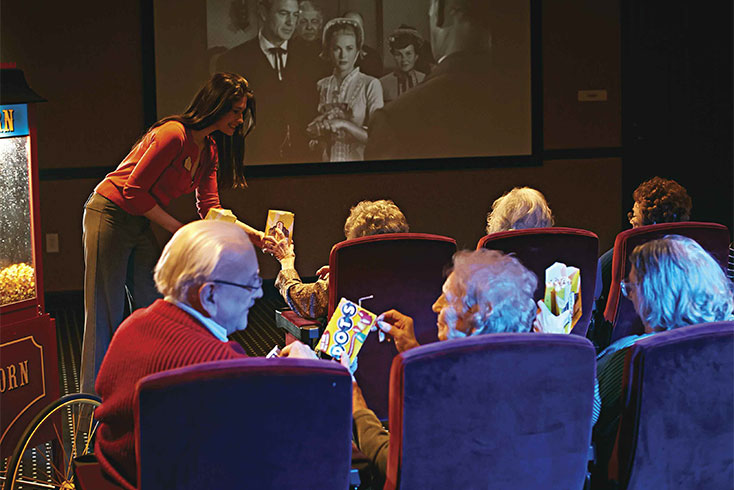 A film showing in the movie room with popcorn, candy and plenty of theatre seating.