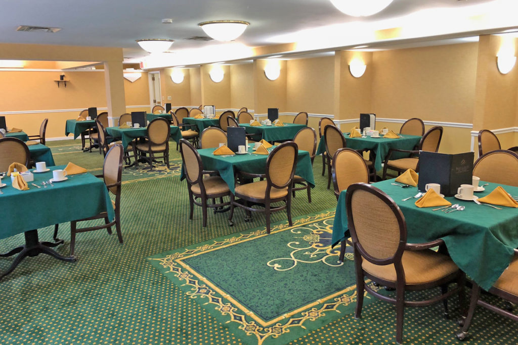 a large dining room with green placemats set with folded napkins and elegant chairs