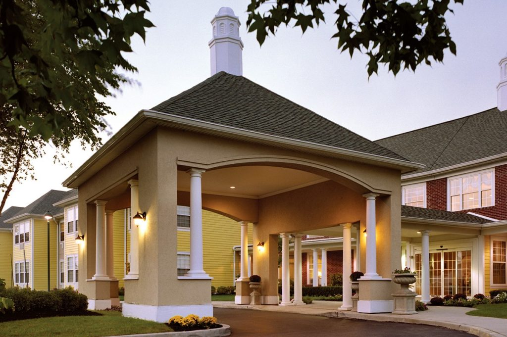Exterior shot of the entrance of Huntington Terrace with large columns and an ornate roof.
