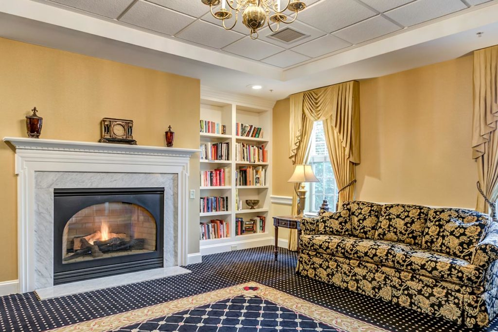 Communal living room with a fireplace, comfortable couch, and plenty of books