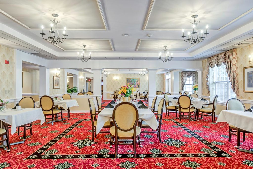 Ornate dining room with red carpet, many chandeliers, crown molding, and well-decorated tables.