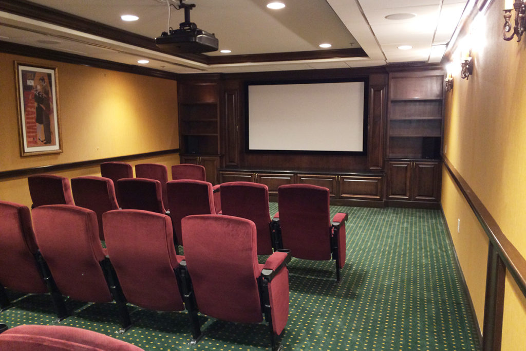 Movie theater room with a large projector screen and plenty of theater seating