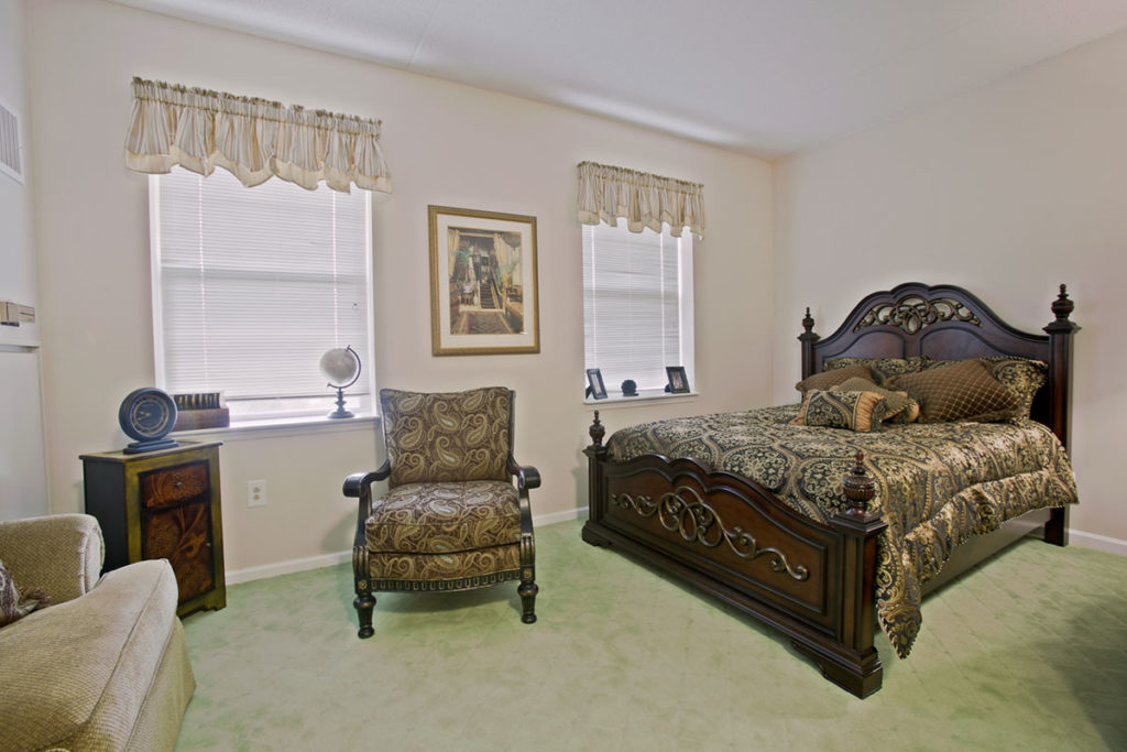 Brandywine Living at The Sycamore example of a resident room with a 4 post bed and a easy chair