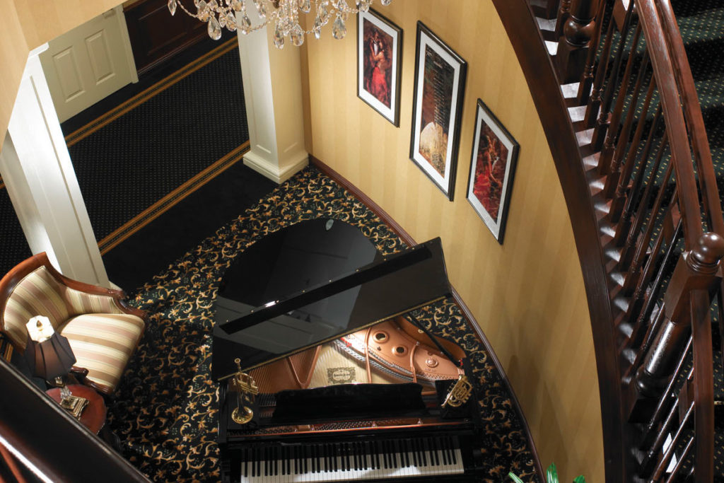 grand piano near the staircase in the lobby for guests