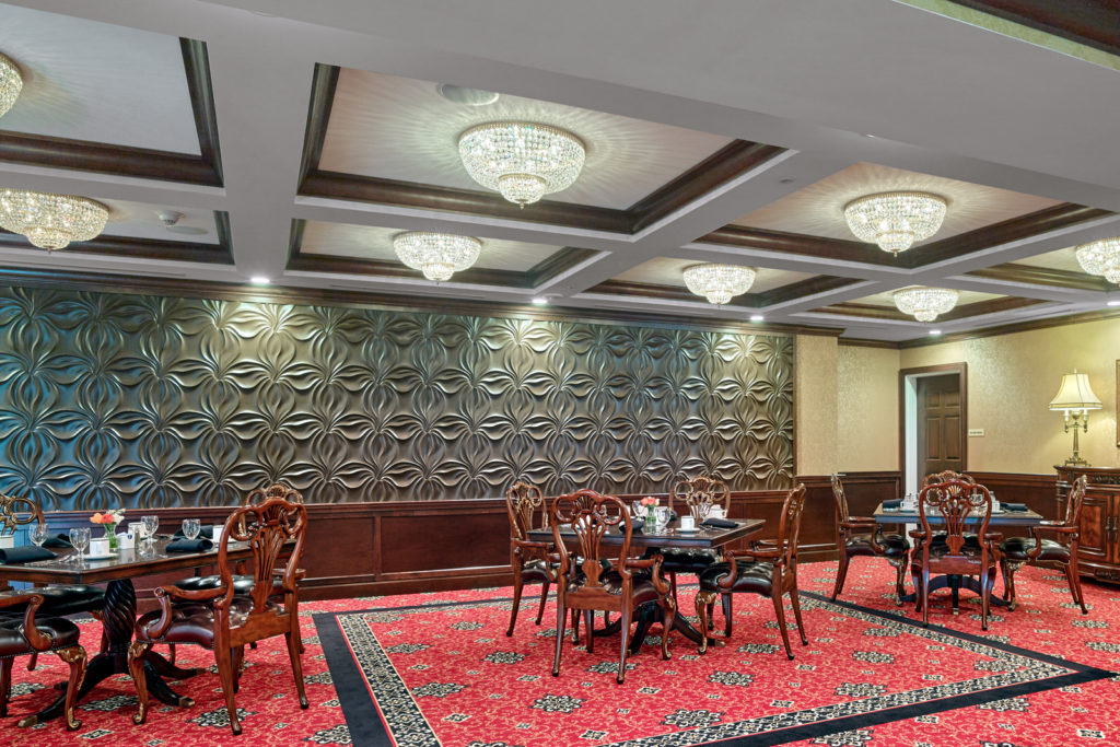 Room with molded ceilings, chandeliers, and plenty of seating for activities.