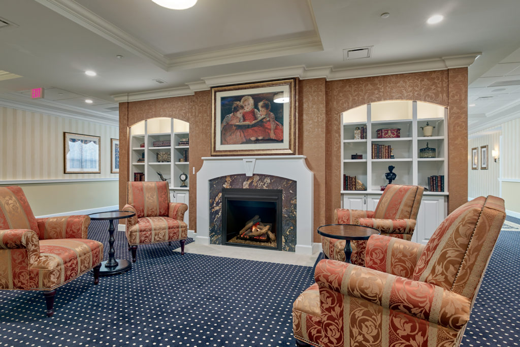 A guest lounge room with built-in book cases and a fireplace.