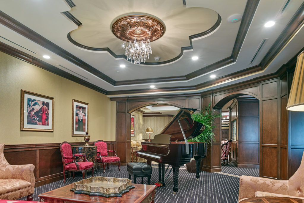 Music room with a baby grand piano, and molded ceilings.