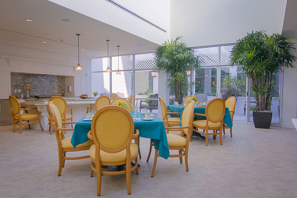 dining area with blue table cloths, a lot of natural lighting, and green trees.
