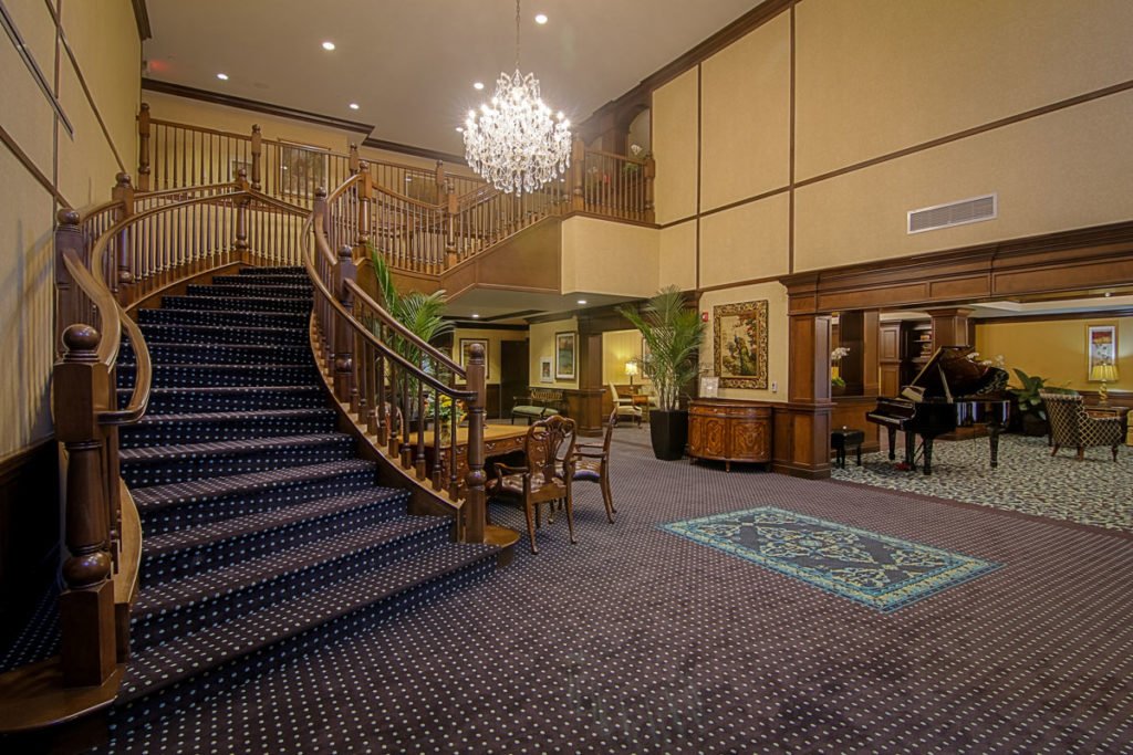 Grand staircase in the entry way of the lobby with a large chandelier.