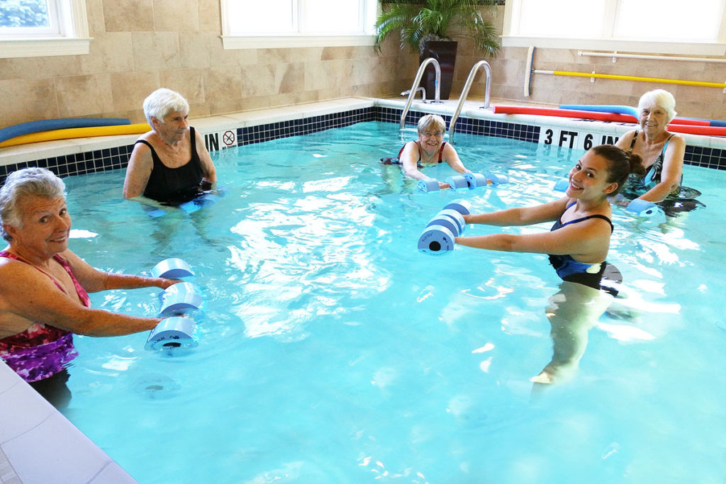 Aquatic therapy in the pool on site with multiple residents staying active.