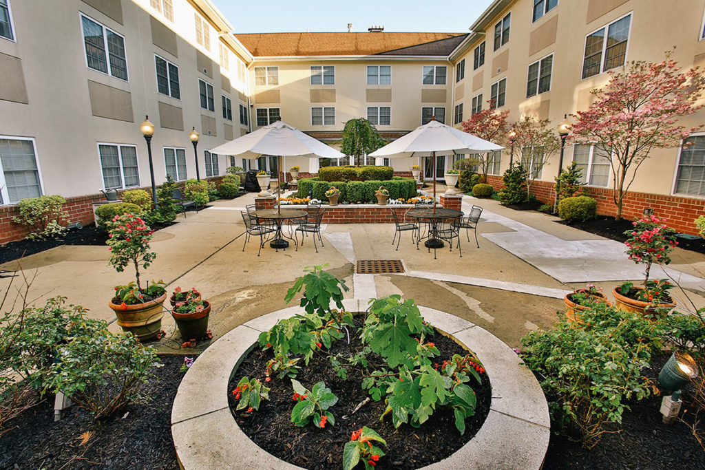 Brandywine Living at Mountain Ridge courtyard with tables and greenery