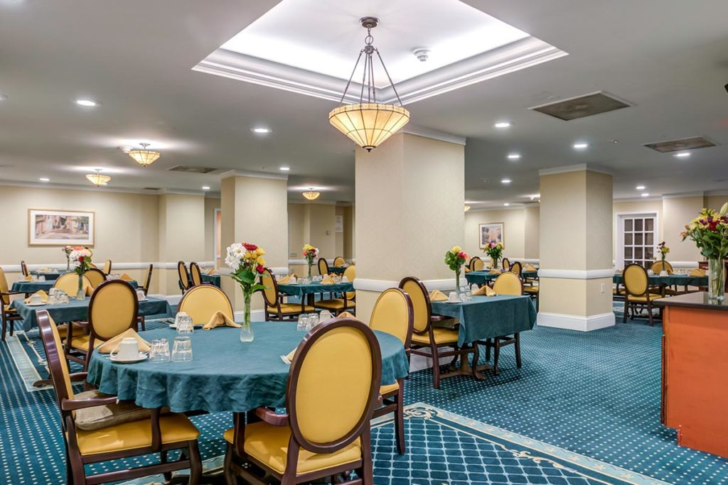 Dining hall with blue carpet and gold chairs set up nicely for residents to eat.