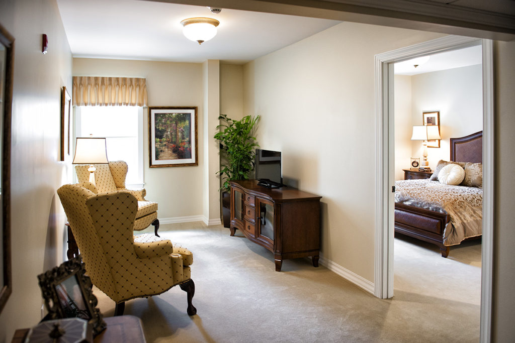 suite with chairs, desk and a view of the bedroom