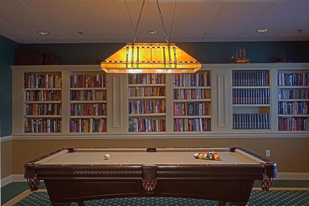 Billiards room with a pool table and built in book shelves full of books.