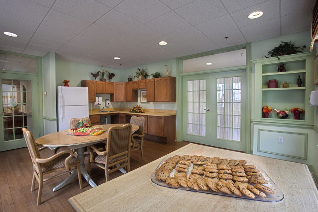 Community Cafe with seating, a fridge, and kitchen appliances as well as a tray of cookies.