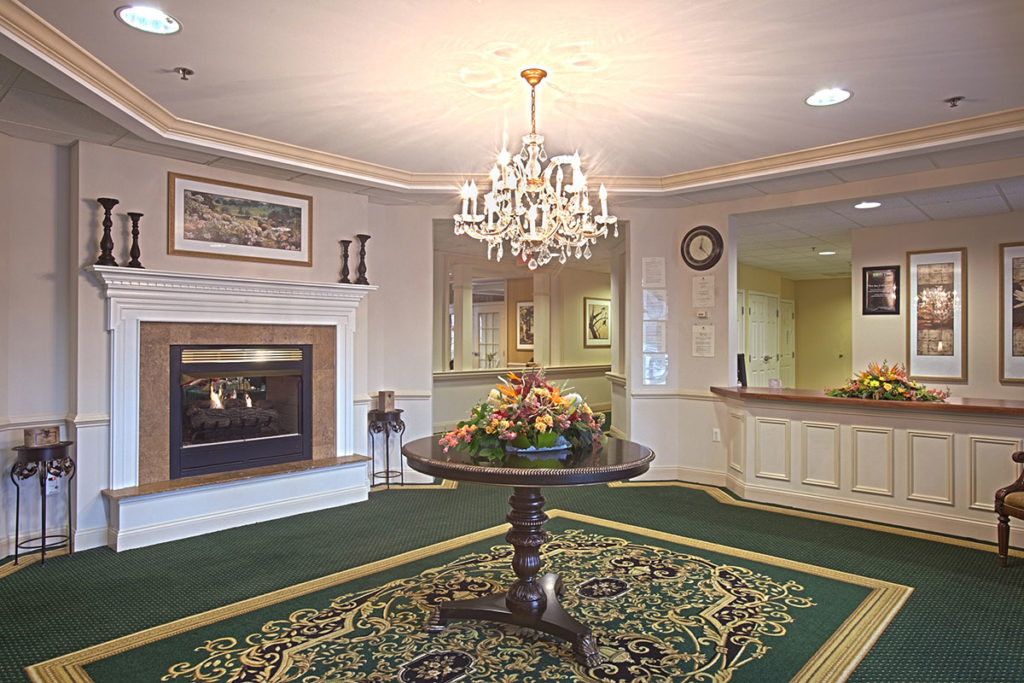 The lobby at Howell with a large fireplace, a chandelier, and ornate carpets.