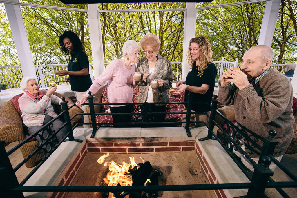 Brandywine Living at The Sycamore residents and guests standing around a firepit drinking hot chocolate