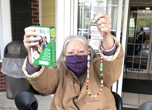 Senior Woman Holds Up Cookies and Mask Chain