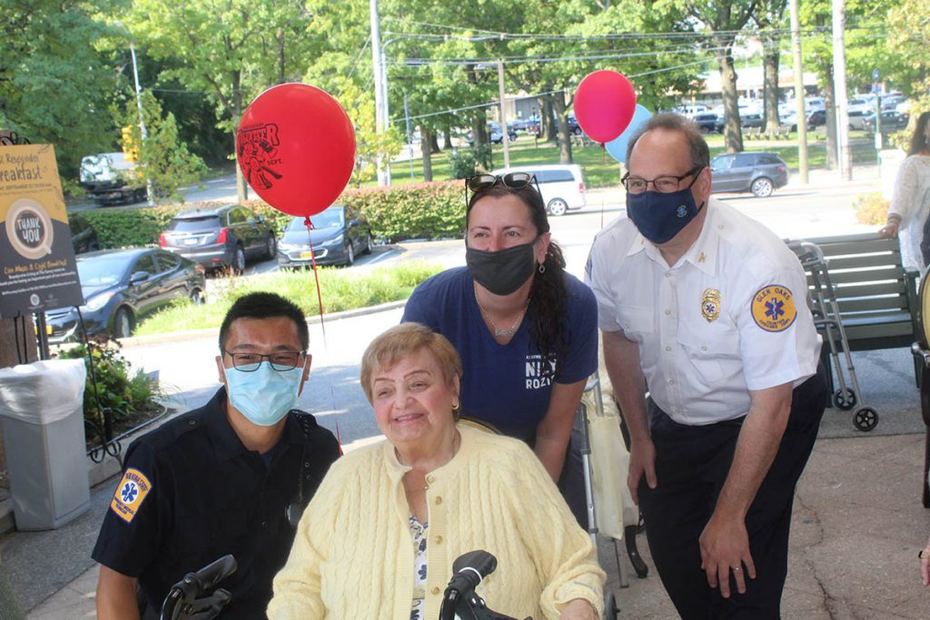 Assemblywoman Nily Rozic with Resident Council President Helaine Rossett and local first responders.